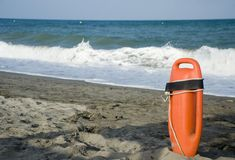 Life buoy. Lifeguard's rescue equipment stands at ready on beach Stock Photos