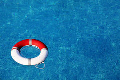 Life buoy. Red life buoy floating in swimming pool Stock Photo