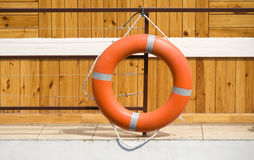Life buoy. Red life buoy hanging on a wooden wall Stock Photography