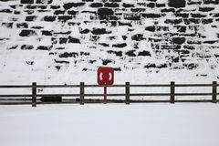 Life buoy at base of dam in the snow Stock Image
