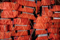 Many stacked lifejackets. Life buoy in the boat stock images