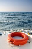 Life buoy on the boat sailing in the sea. Life buoy on the sailing boat with calm sea and blue sky above Royalty Free Stock Photos