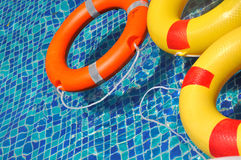 Life buoy floating in swimming pool. Colorful life buoy floating in blue color swimming pool, shown as spare time or holidy enjoying and beautiful color of rings Royalty Free Stock Photo