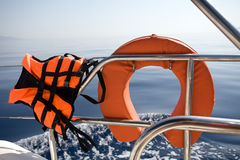 Life buoy and life jacket. Closeup on sea water background Royalty Free Stock Photography