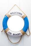 Life buoy mirror isolate with welcome on board on white wood doo Stock Photo