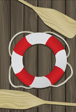 Life Buoy and Oar Background. Life Buoy and two Boat Oars on a deck background Royalty Free Stock Image