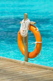 Life Buoy. Orange  lifebuoy or lifebelt hanging in pole on boardwalk at a resort in Maldives Stock Image