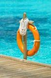 Life Buoy. Orange lifebuoy or lifebelt hanging in pole on boardwalk at a resort in Maldives stock image