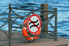 Life buoy on a pier with sign prohibiting usage during waves.  Stock Image