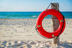 Life buoy on a pole on a beach in Mexico Stock Photos