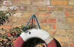 Life Buoy preserver attached to a red brick Wall with Copy Space Royalty Free Stock Images