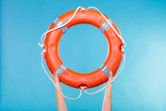 Life buoy ring in female hands. Accident prevention and water rescue. Life buoy ring lifebelt in female hands studio shot blue background Stock Photo