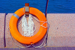 Life buoy. With rope fixed on the wall near sea Stock Photo