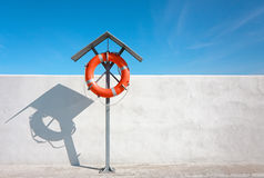 Life buoy for safety. Orange life buoy on the rack at the breakwater against blue sky.  Safety equipment. Simplistic scene Royalty Free Stock Images