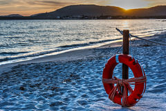 Life buoy by the sea at sunset Royalty Free Stock Photography
