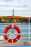 Life buoy on ship rail, view to Christ the King statue Royalty Free Stock Photos
