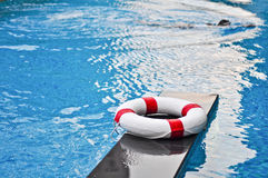 Life buoy in the swimming pool. And woman is swimming in the pool Royalty Free Stock Photos