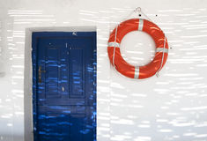 Life buoy on the wall. Red life buoy on the white wall Royalty Free Stock Image