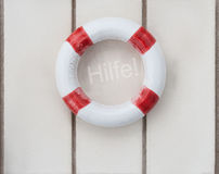 Life buoy. Wooden life buoy on wood with the word Hilfe (german word for help Royalty Free Stock Photography