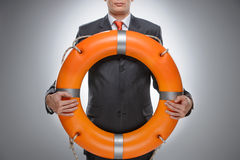 Life buoy for your business. Businessman holding a life belt while isolated on gray. Life buoy for your business. Businessman holding a life belt while on gray royalty free stock image