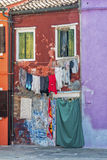 Daily life on Burano, Italy. Laundry in front of colorful houses in a street on the beautiful Island of Burano in Italy, july 2015 Stock Image
