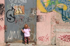 Life in a city. Lonely baby standing opposite to the wall with graffiti and closed door Stock Images
