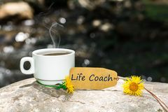 Life coach text with coffee cup. Life coach text in tag with coffee cup and yellow flower on rock in the river , shine bokeh background royalty free stock image