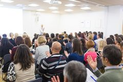 Woman giving interactive motivational speech at entrepreneurship workshop. Royalty Free Stock Image