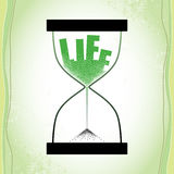 Life concept with hourglass and decreasing sand on the textured green background Royalty Free Stock Photography