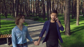 Life with devices in nowadays. Family walking in a park. Busy husband has conversation with client on smartphone. Upset woman looking on man. Gadgets in modern stock footage
