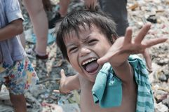 Life on the dump site. A little boy very happy to have his photo taken, while living on a dump site in the Philippines he still treasures and enjoys life Royalty Free Stock Image