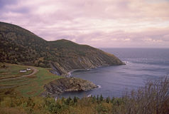 Life at End of  World. Meat Cove, Nova Scotia is the Northern-most settlement of Cape Breton Island. A solitary house sits on the rugged mountain coast at sunset Stock Photos