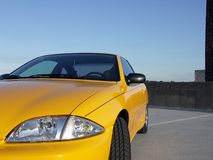 Life in the Fast Lane. Yellow Sports Car on top of a parking deck at sunset Royalty Free Stock Photography
