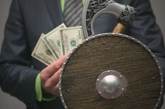 Life or finance insurance agent. Money deposite safety agent. Businessman holds in hand a toy viking axe weapon and shield. Life or finance insurance agent Stock Photography