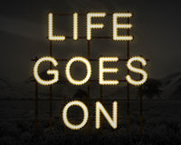 Life Goes On inspiring text in lights against dark landscape background. Life Goes On inspirational text in lights against dark landscape background stock photos