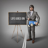 Life goes on text on blackboard with businessman Stock Images
