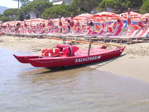 Life Guard boat on an Italian Beach. A life guards boat lies on an Italian Boach at the waterline. Rows of sunbeds and umbrellas are behind royalty free stock photos