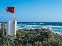 Life Guard Flag Beach Florida. Red Life Guard Flag flying in the wind - Room for copy stock photos