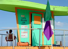Life Guard Life. Close up of Life Guard Tower on South Miami Beach, Florida, with lifeguard kicking back but keeping watch Royalty Free Stock Images