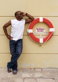 A Black male  poses next to life ring Royalty Free Stock Photos