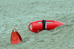 Life Guard Rescue Buoy and Flippers Life Saving. Red life guard life saving rescue buoy and flippers sitting in sand ready to go if needed. A rescue buoy, also Royalty Free Stock Photography
