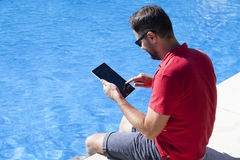 Life guard using tablet sitting on the poolside. Stock Photography