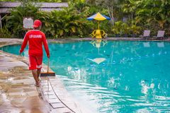 Life guard wearing red uniform working/walking around poolside keeping an eye on things at public pool in Asia royalty free stock photography