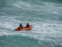 Life guards in a zodiac on wavy ocean. Rescue patrol, Auckland, New Zealand Royalty Free Stock Photography