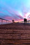 Life happening on the pier in San Clemente under pink and  turquoise sky Royalty Free Stock Photo