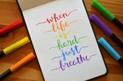 WHEN LIFE IS HARD JUST BREATHE hand-lettered in notebook. With brush pen and cup of coffee on wooden desk Royalty Free Stock Image