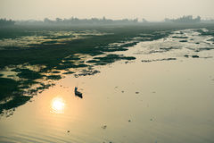 Life of India : Fishing boat in a sunset river Stock Photos