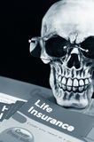 Life insurance. Human skull with glasses reading life insurance information Stock Image