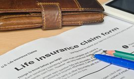 Life insurance claim form on a wooden surface