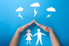 Life insurance and family health concept. Hands protect paper figures origami from lightning from the clouds on blue background. Man and woman holding hands stock images
